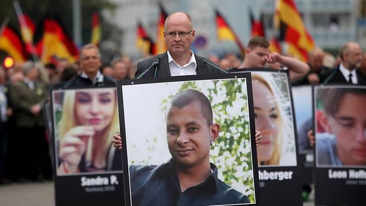 Ein Mann hält bei einer Demonstration in Chemnitz ein Bild des Ende August mutmasslich von ausländischen Migranten erstochenen Opfers. (Archivbild)