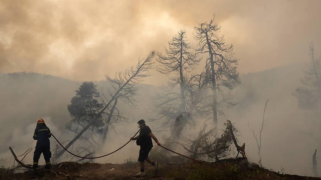 Zwei Männer versuchen im Dorf Ellinika auf der Insel Euböa die Flammen zu löschen. Nach über einer Woche Kampf gegen unzählige Großbrände im ganzen Land hat sich die Situation in Griechenland am Montag vorerst leicht entspannt. Doch die Gefahr ist nicht gebannt. Foto: Petros Karadjias/AP/dpa