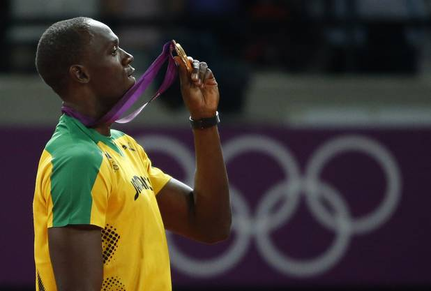 Jamaica's Usain Bolt holds up his gold medal for the men's 200-meter during the athletics in the Olympic Stadium at the 2012 Summer Olympics, London, Thursday