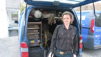 Kaminfegerin auf Achse: Sandra Haslebacher vor dem Bus, indem sie das Material für ihren Arbeitsalltag dabei hat.