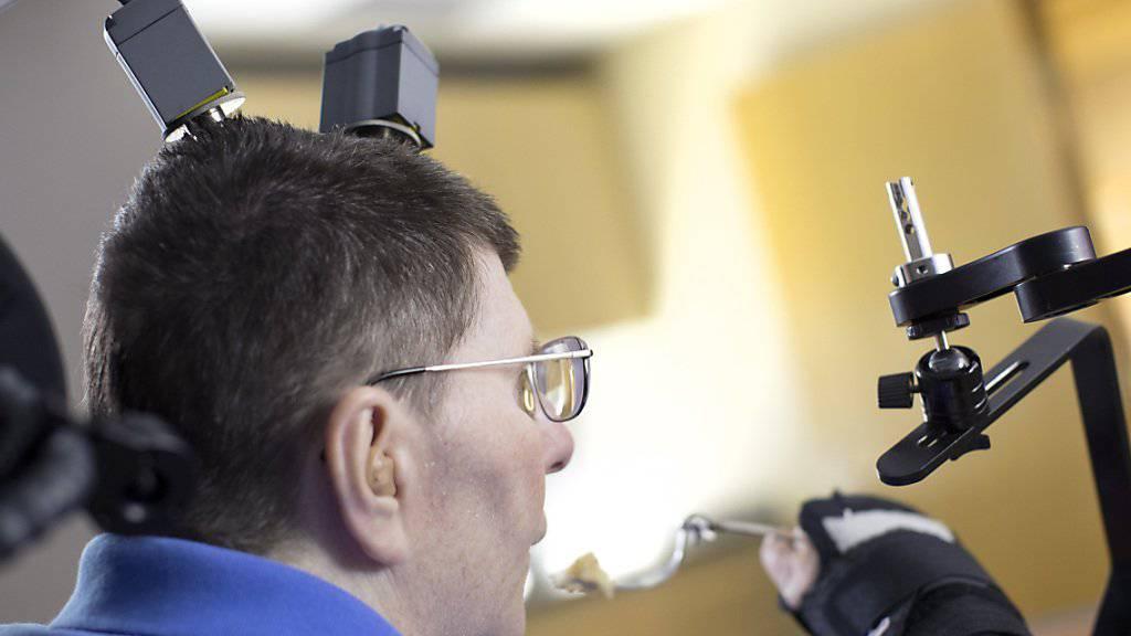 Bill Kochevar, der bei einem Fahrradunfall vor 10 Jahren von den Schultern abwärts gelähmt wurde, kann nach einer neuartigen Behandlung wieder einen Löffel benutzen und Kaffee nippen.