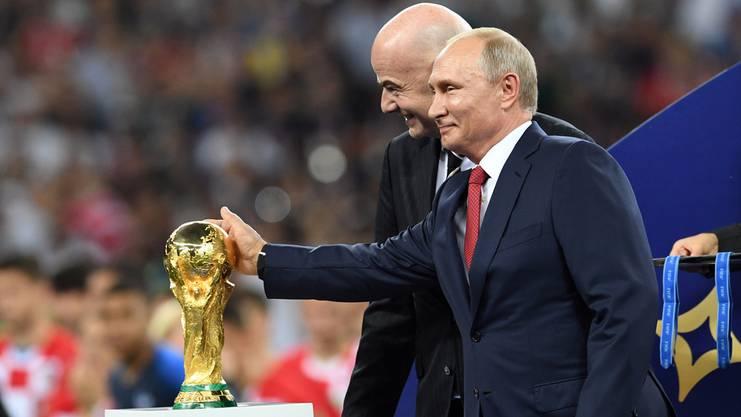 Putin streichelt den Pokal. Infantino grinst.