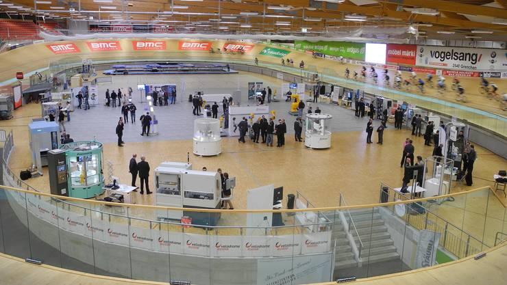 Aussen surren Radfahrer, innen Roboter an der 2. Robotermessse im Velodrome.