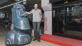 Zwischen dem 3-D-Drucker mit der schwarzen Verglasung (r.) und dessen gedruckter Moai-Statue wirkt Firmeninhaber Claude Lombard fast schon klein.