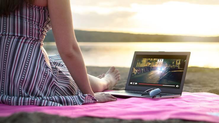 Gemütlich ein Film streamen am Strand. Ein Schweizer Filmverleih will, dass die Swisscom illegale Streamingseiten mit einer Netzsperre belegen müssen.