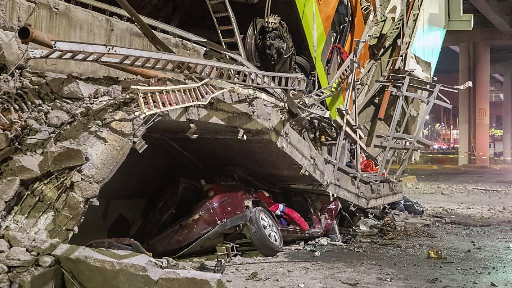 Ein Auto liegt unter Trümmern, nachdem ein Brückenabschnitt der U-Bahn-Linie 12 in Mexiko-Stadt zusammengebrochen war. Zwei Waggons stürzen auf eine viel befahrene Strasse.