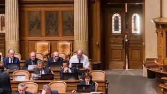 Mitglieder des Nationalrats im Saal, während draussen die Frühlingssonne scheint.