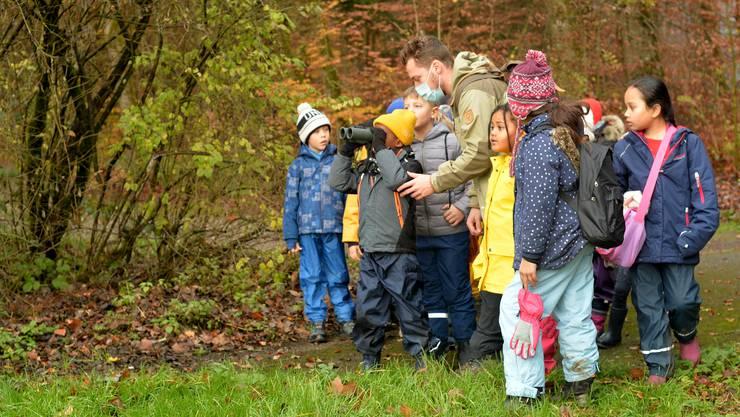 Draussen lernen die Kinder, wie man richtig durch einen Feldstecher guckt.