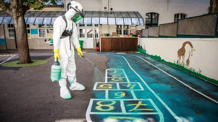 Ein Reinigungsarbeiter versprüht Dekontaminierungsmittel in der St.-Benoit-Primarschule in Paris.
