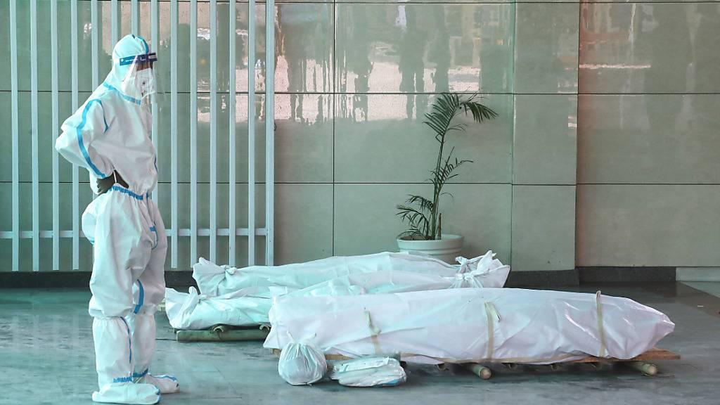 Ein Angehöriger steht in einem indischen Krematorium vor dem Leichnam eines verstorbenen Corona-Patienten. Foto: Naveen Sharma/SOPA Images via ZUMA Wire/dpa