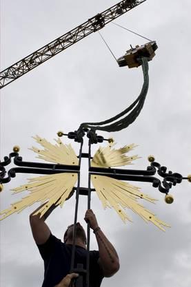 Das Eisenkreuz mit vergoldetem Strahlenkranz wird am Kran angehängt