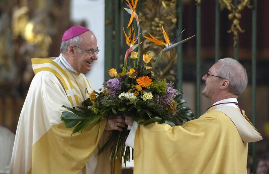 Der frühere St.Galler Bischof Ivo Fürer, links, freut sich über einen Blumenstrauss, den ihm Generalvikar Josef Rosenast überreicht. (Bild: KEYSTONE/Regina Kühne)