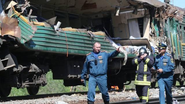 Rettungskräfte vor einem völlig zerstörten Wagen des Passagierzugs