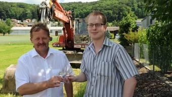 Rolf Merz und Roger Hochstrasser stossen während des Spatenstichs auf den Erweiterungsbau an