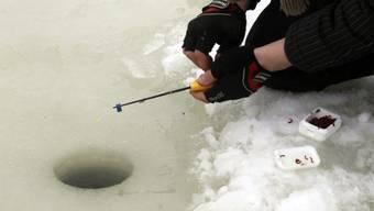 Ein Eisfischer während eines Wettbewerbes in Estland (Archiv)