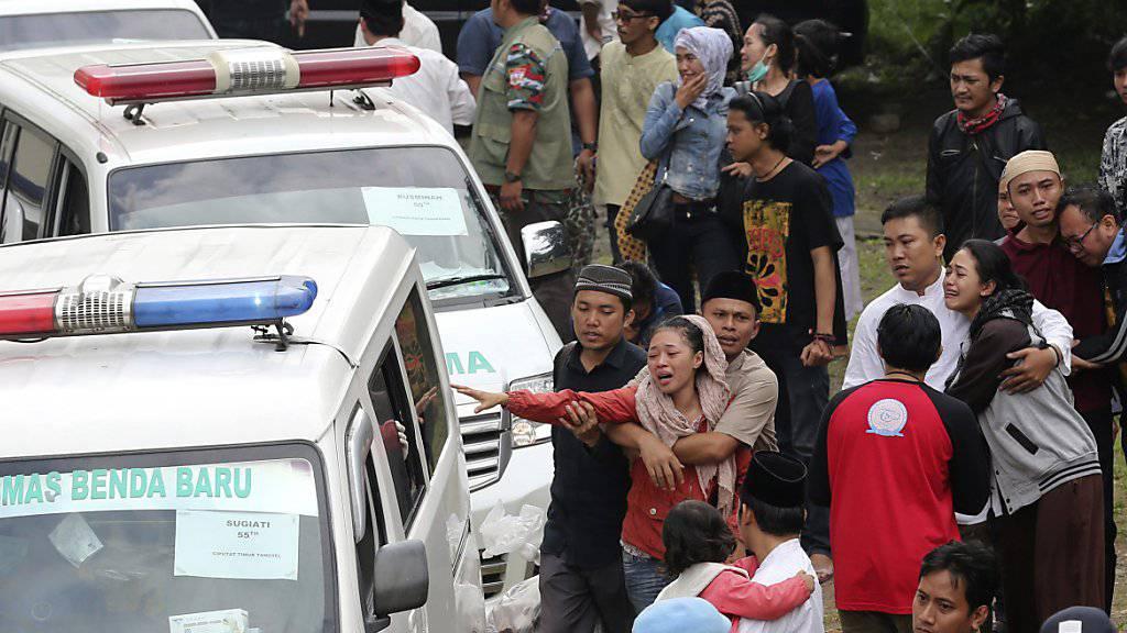 Angehörige brechen in Tränen aus, als Ambulanzen mit den Opfern des Busunfalles im Heimatdorf im indonesischen East Ciputat eintreffen.