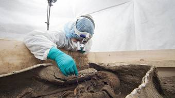 Forschende des Römermuseums Augusta Raurica legen das Skelett der älteren, wohlhabenden Frau im Bleisarg frei.