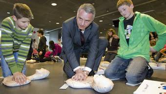 Bundesrat Didier Burkhalter übt die Herzmassage an einer Puppe (2010).