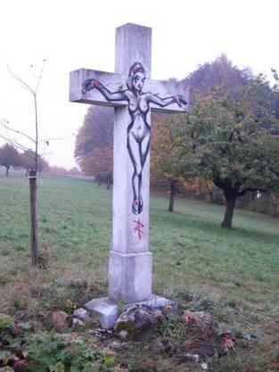 Eine nackte Frau wurde auf das beschädigte Kreuz gesprayt.