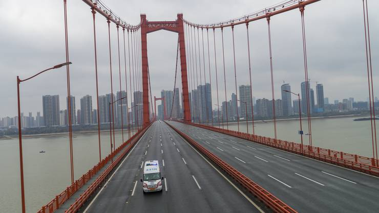 Eine Ambulanz unterwegs auf einer leeren Brücke in Wuhan am Samstag, 25. Januar.