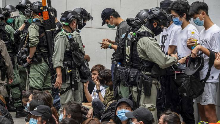 Polizisten durchsuchen die Taschen von Aktivisten in Hongkong.