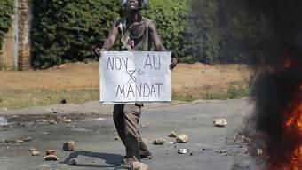 Ein Demonstrant hält ein Plakat, mit dem er gegen eine dritte Amtszeit von Burundis Präsident Nkurunziza protestiert