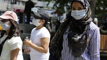 Eine Frau und Kinder tragen Mundschutz bei einem Spaziergang in einem öffentlichen Garten. Foto: Burhan Ozbilici/AP/dpa