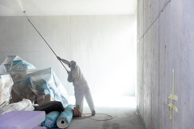 Im Innern des Gebäudes wird fleissig gearbeitet. Ein Handwerker besprayt die Decke in der künftigen Coop-Filiale mit Grundierungsfarbe.