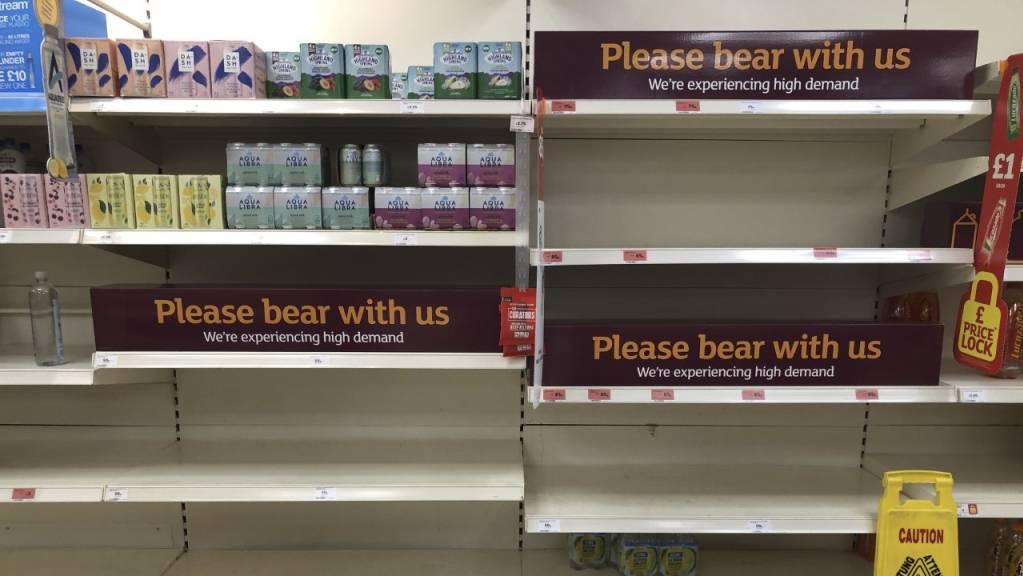 Blick auf leere Regale und Schilder in einem britischen Supermarkt. Die hohe Zahl an Menschen in coronabedingter Quarantäne stellt Großbritannien vor Herausforderungen. Wegen massiver Personalausfälle hat die britische Regierung die Quarantäne-Regeln für einige Berufsgruppen gelockert. Foto: Matthew Cooper/PA/AP/dpa