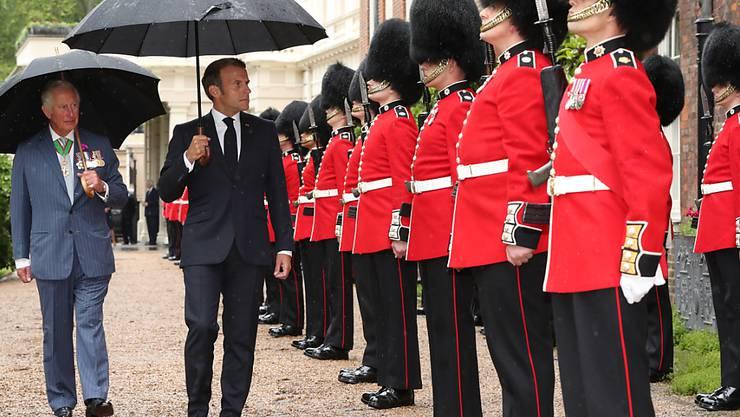 Der britische Prinz Charles (l), Prinz von Wales, und Emmanuel Macron (M), Präsident von Frankreich, gehen bei der Willkommenszeremonie die Grenadier-Garde im Clarence House ab. Foto: Jonathan Brady/PA Wire/dpa