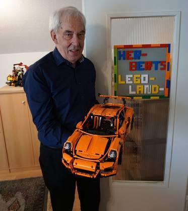 Herbert Hunziker posiert mit seinem Lego-Porsche vor der Eingangstür seines Legolandes.