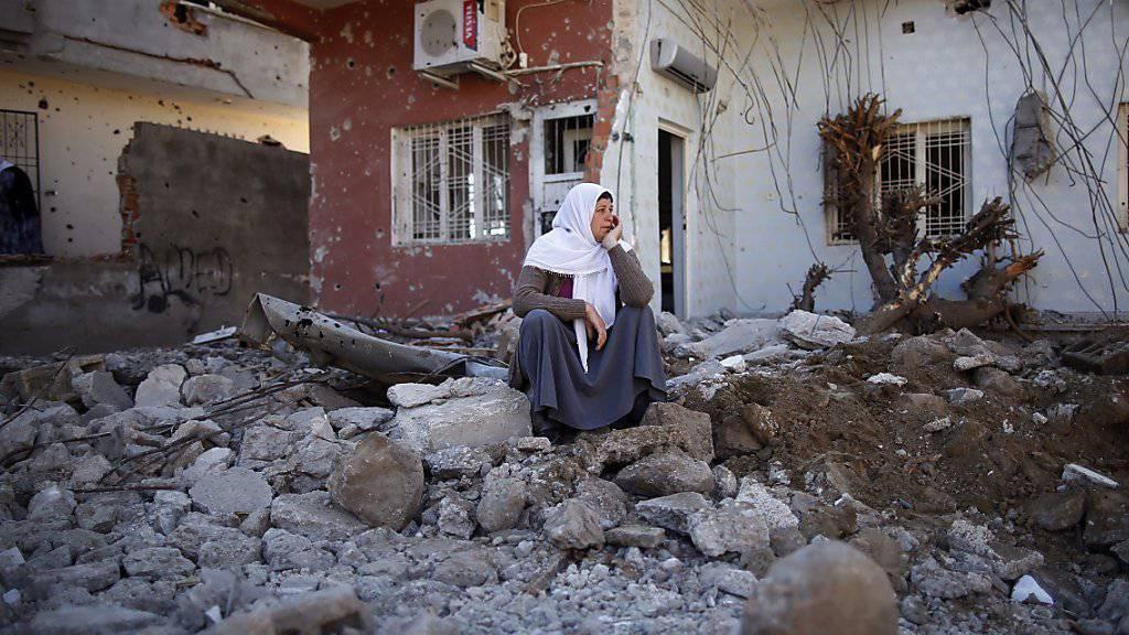 Ein Frau sitzt inmitten der Trümmer ihres zerstörten Hauses in Cizre. Nach wochenlangen Kämpfen ist das Ausgehverbot in der Stadt aufgehoben worden.