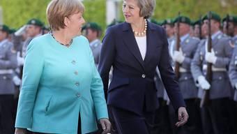 Bundeskanzlerin Merkel (links) schreitet mit der neuen britischen Premierministerin May die Ehrengarde in Berlin ab.