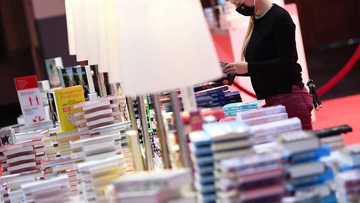 Eine Mitarbeiterin der Frankfurter Buchmesse steht vor der Eröffnungspressekonferenz der Frankfurter Buchmesse an einem Buchstand in der Festhalle. Foto: Arne Dedert/dpa pool/dpa