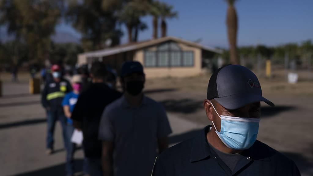 Eingewanderte Landarbeiter tragen Mund-Nasen-Bedeckungen und warten in einer Schlange, um die Corona-Impfung zu erhalten. Verbände warnen davor, dass Millionen Einwanderer zu den am schwierigsten zu erreichenden Menschen während der größten Impfkampagne in den USA gehören könnten. Foto: Jae C. Hong/AP/dpa