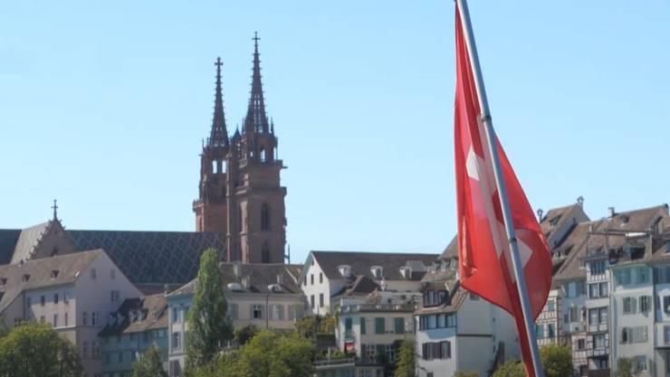 Blick von der Mittleren Brücke mit Schweizer Flagge auf das Basler Münster.
