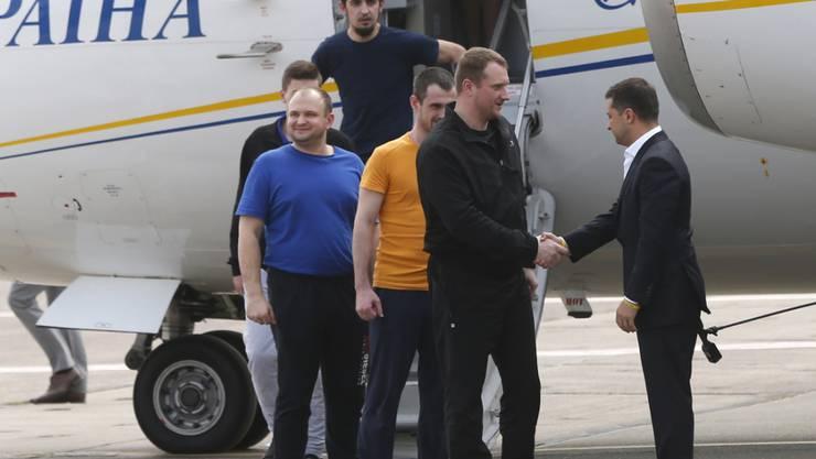 Der ukrainische Präsident Wolodymyr Selenskyj (r) nahm die ukrainischen Freigelassenen persönlich auf dem Rollfeld in Kiew in Empfang.