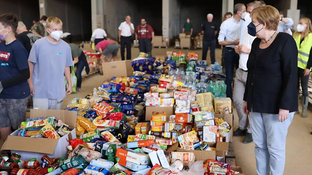 dpatopbilder - Bundeskanzlerin Angela Merkel besichtigt ein Lager mit Lebensmitteln bei ihrem Besuch im vom Hochwasser betroffenen Gebiet von Bad Münstereifel. Foto: Oliver Berg/dpa-Pool/dpa