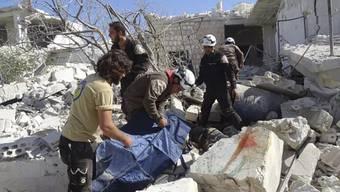 """Retter durchsuchen Gebäudetrümmer nach Luftangriffen auf die Stadt Idlib. Nach Informationen der UNO-Kinderhilfswerks wurden bei einem Angriff auf eine Schule mindestens 22 Kinder getötet. Das Foto wurde von der syrischen Gruppe """"White Helmets"""" zur Verfügung gestellt."""