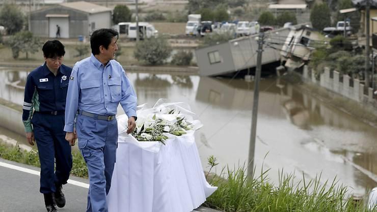 Ministerpräsident Shinzo Abe bei einem Besuch in den japanischen Überschwemmungsgebieten. (Archiv)
