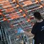Ein Mitarbeiter eines Ladens in Salzburg desinfiziert Einkaufswagen. (Archivbild)