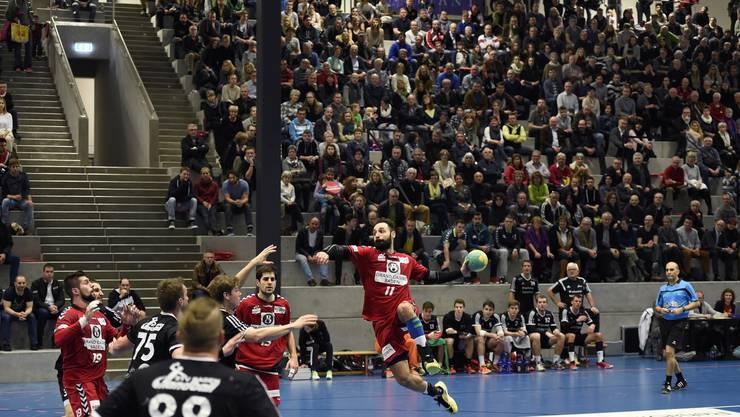 Nemanja Sudzum (am Ball, Endingen) beim Sprungwurf in der prallgefüllten Go easy Arena in Station Siggenthal.