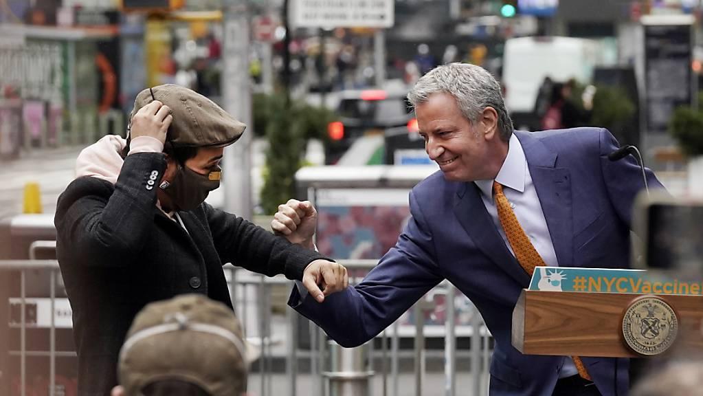 Der Schauspieler Lin-Manuel Miranda (l) und Bill de Blasio, Bürgermeister von New York, stossen auf dem Times Square die Ellbogen aneinander. (Archiv)