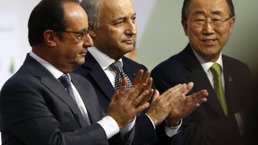 Frankreichs Präsident François Hollande, Aussenminister Laurent Fabius und UNO-Generalsekretär Ban Ki Moon applaudieren bei der Vorlage des Schlusstextes für das Klima-Abkommen.