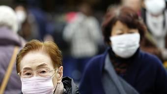 Menschen tragen Gesichtsmasken in einem Einkaufsviertel in Tokio. (Archivbild)