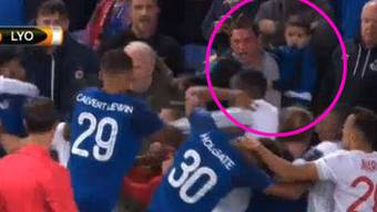 Rudelbildung zwischen Everton- und Lyon-Spieler: Ein Vater mit Kind auf dem Arm eilt zum Gerangel und greift auch noch ein.