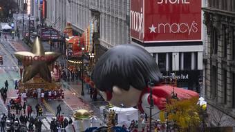 Festzugswagen ziehen bei der Festtagsparade «Macy's Thanksgiving Day Parade» durch die Straßen. Foto: Craig Ruttle/AP/dpa