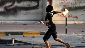 Ein Demonstrant wirft eine Benzinbombe gegen Polizisten in Dahi, Bahrain