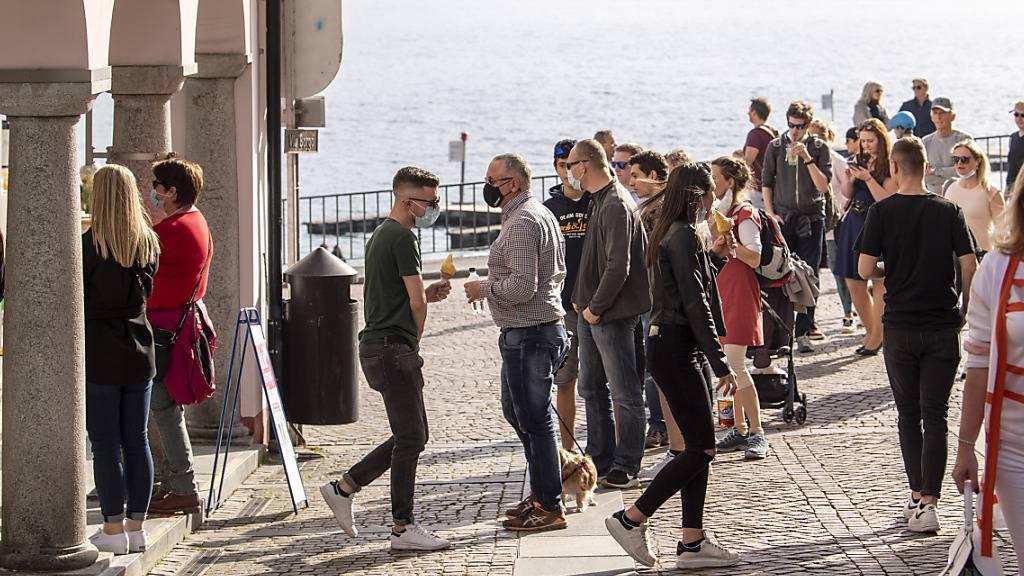 Frühling in Zeiten der Pandemie: Menschen stehen bei der Seepromenade in Ascona Schlange, um eine Glacé zu kaufen.
