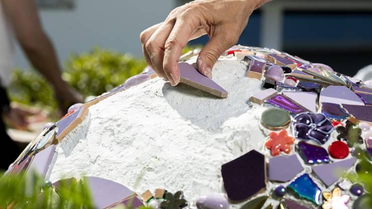 Das Mosaik besteht aus verschiedenen Materialien wie Natursteinen und Keramik.